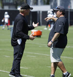 Oakland Raiders coach Jon Gruden, left, speaks with defensive coordinator Paul Guenther during NFL football practice on Tuesday, June 4, 2019, at the team's training facility in Alameda, Calif. (AP Photo/Ben Margot)