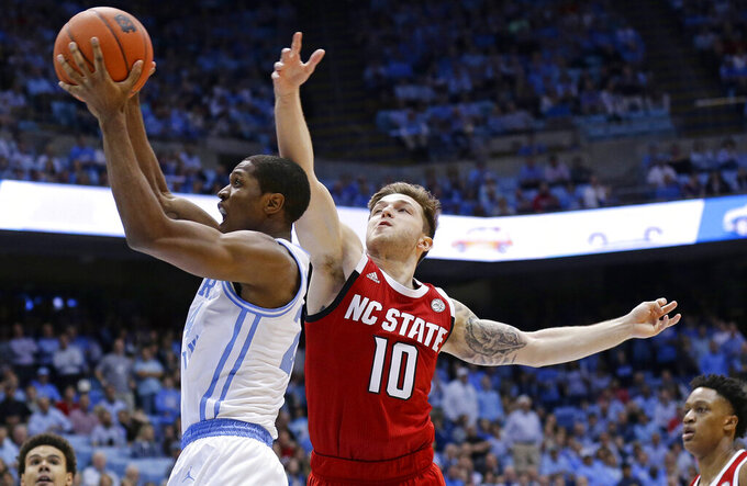 North Carolina's Kenny Williams, left, shoots while North Carolina State's Braxton Beverly, right,  defends during the first half of an NCAA college basketball game in Chapel Hill, N.C., Tuesday, Feb. 5, 2019. (AP Photo/Gerry Broome)