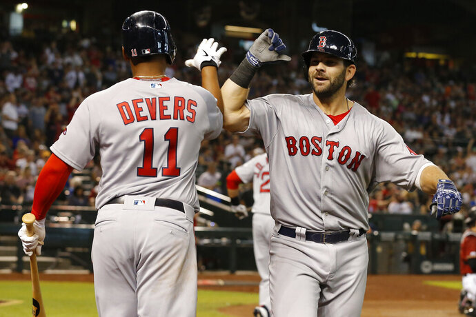 Boston Red Sox's Mitch Moreland celebrates with Rafael Devers (11) after hitting a solo home run against the Arizona Diamondbacks in the seventh inning of a baseball game, Sunday, April 7, 2019, in Phoenix. (AP Photo/Rick Scuteri)