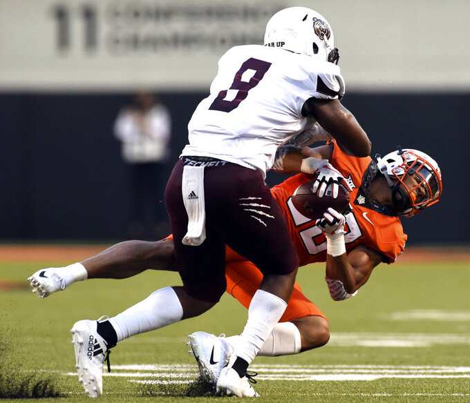Missouri State linebacker Angelo Garbutt, left, shoves Oklahoma State running back Chuba Hubbard, right, to the ground during the first quarter of an NCAA college football game in Stillwater, Okla., Thursday, Aug. 30, 2018. (AP Photo/Brody Schmidt)