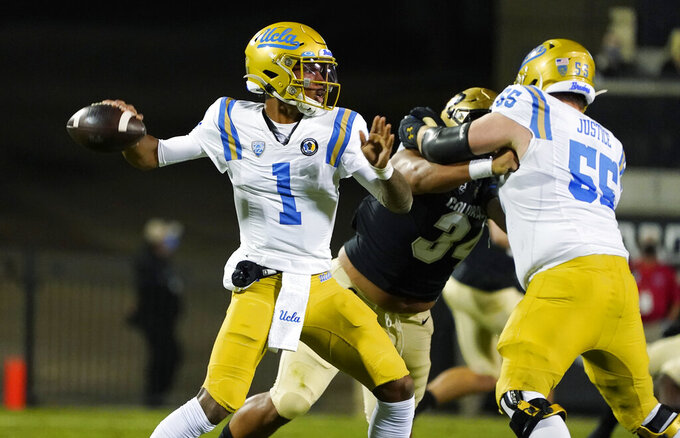 UCLA quarterback Dorian Thompson-Robinson, left, looks to pass the ball as Colorado defensive end Mustafa Johnson, center, fights for position with UCLA offensive lineman Paul Grattan, right, in the first half of an NCAA college football game Saturday, Nov. 7, 2020, in Boulder, Colo. (AP Photo/David Zalubowski)