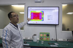 In this Aug. 21, 2019, photo, a Huawei research engineer describes the work done at the Huawei Thermal design lab in Dongguan in Southern China's Guangdong province. Facing a ban on access to U.S. technology, Chinese telecom equipment maker Huawei is showing it increasingly can do without American components and compete with Western industry leaders in pioneering research. (AP Photo/Ng Han Guan)