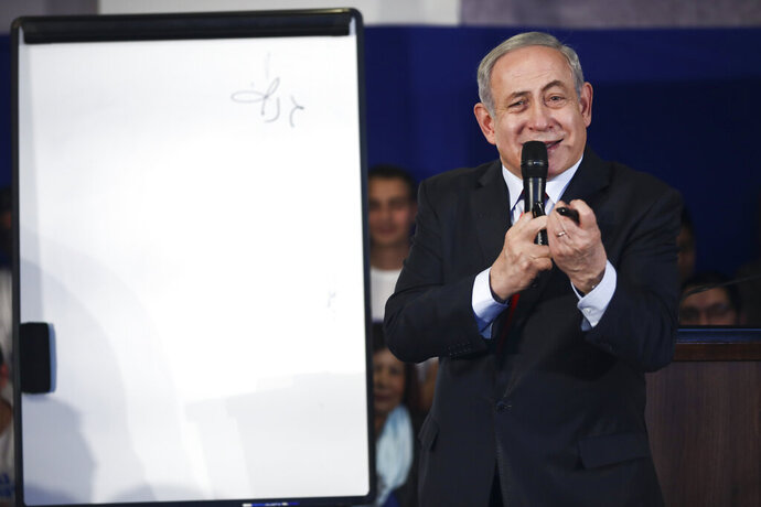 Israeli Prime Minister Benjamin Netanyahu speaks to his supporters during his election campaign speech in Rosh Haain, Israel, Thursday, Feb. 13, 2020. Hebrew on board reads