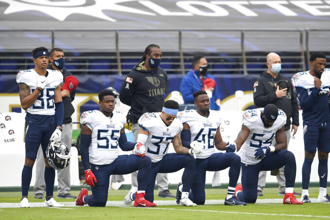 Tennessee Titans players take a knee during the national anthem prior to an NFL football game against the Baltimore Ravens, Sunday, Nov. 22, 2020, in Baltimore. (AP Photo/Nick Wass)