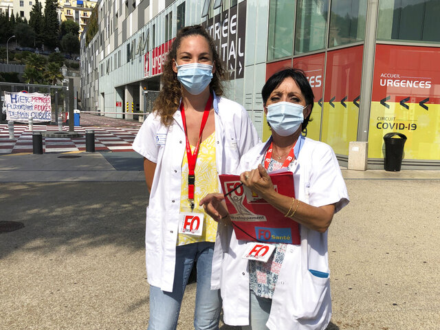 Caregiver Maude Leneveu, left, and union representative Corinne Bryand, pose outside the Pasteur hospital where they work in Nice, southern France, and where the Tour de France is racing this week-end, Friday, Aug. 28, 2020. Both say the race should go ahead, despite increasing infections in France's battle against the coronavirus. (AP Photo/John Leicester)