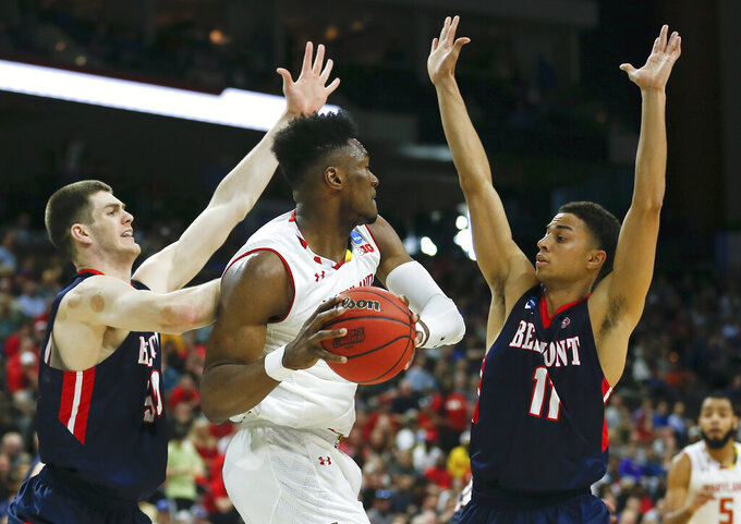Maryland 's Bruno Fernando, center, looks to pass as he is caught between Belmont 's Seth Adelsperger, left, and Kevin McClain (11) during the first half of a first round men's college basketball game in the NCAA Tournament in Jacksonville, Fla., Thursday, March 21, 2019. (AP Photo/Stephen B. Morton)