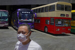 Occupy Central leader Benny Tai stands in front of a vintage double-deck bus used as a polling center for an unofficial