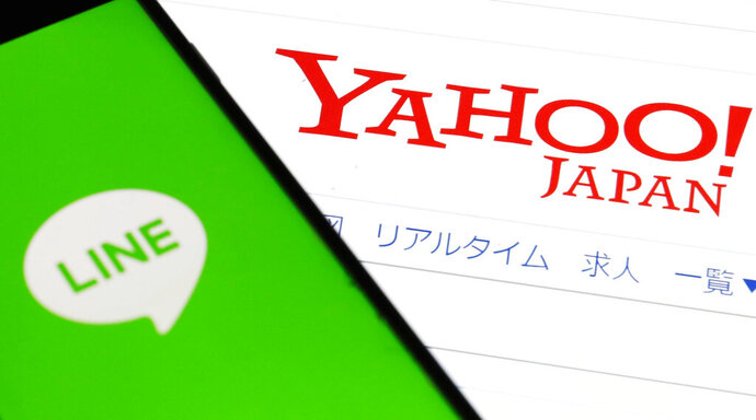This Friday, Nov. 15, 2019, photo shows logs of Yahoo Japan and Line Corp. in Tokyo. The online services announced Monday, Nov. 18, 2019, they are merging. The combination in a joint venture through a tender offer will form an online giant with retail services, advertising and other mobile services such as messaging. (Shinji Kita/Kyodo News via AP)