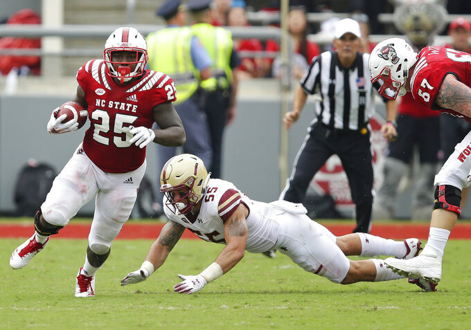 North Carolina State's Reggie Gallaspy II (25) runs the ball as Boston College's Isaiah McDuffie (55) misses the tackle during the first half an NCAA college football game in Raleigh, N.C., Saturday, Oct. 6, 2018. (AP Photo/Gerry Broome)