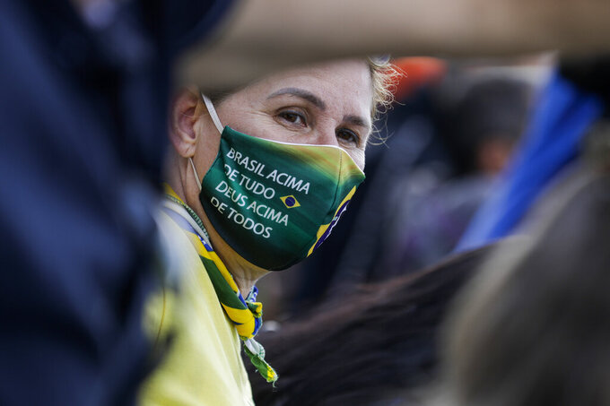 """A supporter of Brazil's President Jair Bolsonaro, wearing a protective face mask with a message that reads in Portuguese: """"Brazil above everything, God above everyone,"""" during a rally of motorcycle enthusiasts who caravanned through the streets of the city, to show their support for Bolsonaro, in Sao Paulo, Brazil, Saturday, June 12, 2021. (AP Photo/Marcelo Chello)"""
