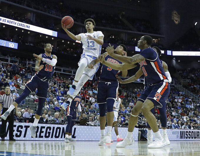 North Carolina's Cameron Johnson (13) heads to the basket as Auburn's Samir Doughty, left, Chuma Okeke and Horace Spencer, right, defend during the first half of a men's NCAA tournament college basketball Midwest Regional semifinal game Friday, March 29, 2019, in Kansas City, Mo. (AP Photo/Charlie Riedel)
