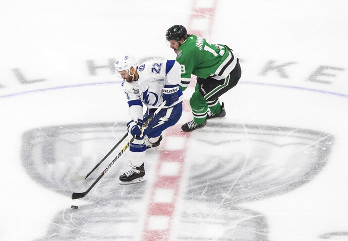 Dallas Stars center Mattias Janmark (13) chases Tampa Bay Lightning defenseman Kevin Shattenkirk (22) during the first period of Game 4 of the NHL hockey Stanley Cup Final, Friday, Sept. 25, 2020, in Edmonton, Alberta. (Jason Franson/The Canadian Press via AP)