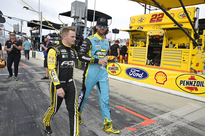 Drivers Justin Haley, left, and Corey LaJoie walk to their cars on pit road before a NASCAR Cup Series auto race at Daytona International Speedway, Saturday, Aug. 28, 2021, in Daytona Beach, Fla. (AP Photo/Phelan M. Ebenhack)