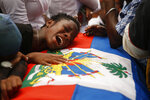 A woman cries on the Haitian flag-draped coffin of a 16-year-old boy killed during a month of demonstrations aimed at ousting President Jovenel Moïse, during a joint funeral for two victims at a public plaza near the National Palace in Port-au-Prince, Haiti, Wednesday, Oct. 16, 2019. Funerals for 11 of at least 20 people killed were held in six cities, including the capital of Port-au-Prince, where at least two people were injured in a protest that broke out when presidential guards tried to block a road near where hundreds had gathered around the coffins of two victims. (AP Photo/Rebecca Blackwell)