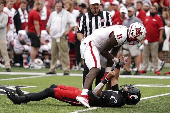 Miami (Ohio) defensive lineman Dominique Robinson (11) helps up Cincinnati quarterback Desmond Ridder, bottom, after a late hit during the second half of an NCAA college football game Saturday, Sept. 4, 2021, in Cincinnati. (AP Photo/Jeff Dean)