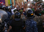 Lebanese retired soldiers shout slogans in front of riot police, as they try to reach the parliament building where lawmakers and ministers are discussing the draft 2019 state budget, in Beirut, Lebanon, Thursday, July 18, 2019. Dozens of protesters have scuffled with Lebanese security guarding the country's parliament just as lawmakers met to vote on a controversial austerity budget. The protesters, most of them army veterans, have been camped near parliament for three days to oppose a draft bill that aims to cut into their pensions, among other measures to reduce public spending.(AP Photo/Hussein Malla)