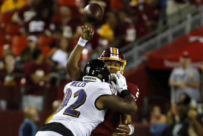 Washington Redskins quarterback Jalan McClendon passes the ball as he is hit by Baltimore Ravens defensive tackle Gerald Willis (92) during the second half of an NFL preseason football game Thursday, Aug. 29, 2019, in Landover, Md. (AP Photo/Alex Brandon)
