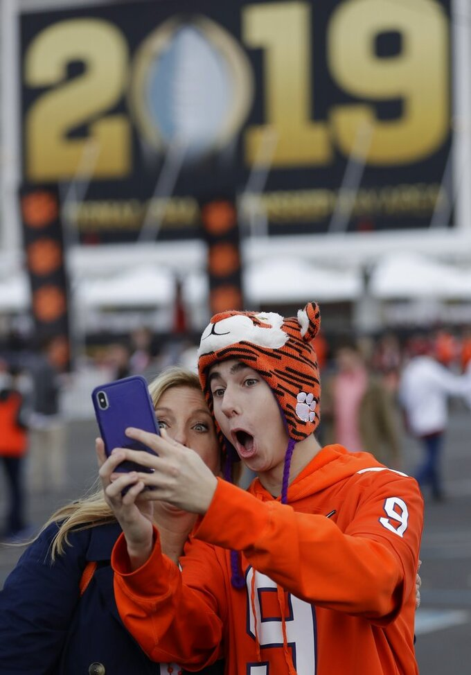 Grayson and Merrell Mann take a selfie outside Levi's Stadium before the NCAA college football playoff championship game between Alabama and Clemson Monday, Jan. 7, 2019, in Santa Clara, Calif. (AP Photo/David J. Phillip)