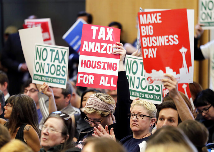 People attending a Seattle City Council meeting hold signs that read
