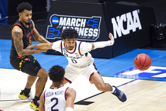 Connecticut's Jalen Gaffney (0) chases down a loose ball next to Maryland's Eric Ayala (5) during the first half of a first-round game in the NCAA men's college basketball tournament Saturday, March 20, 2021, at Mackey Arena in West Lafayette, Ind. (AP Photo/Robert Franklin)