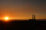 FILE - In this Aug. 19, 2019, file photo shows the sun setting behind the coal-fired Navajo Generating Station near Page, Ariz. (AP Photo/Felicia Fonseca, File)