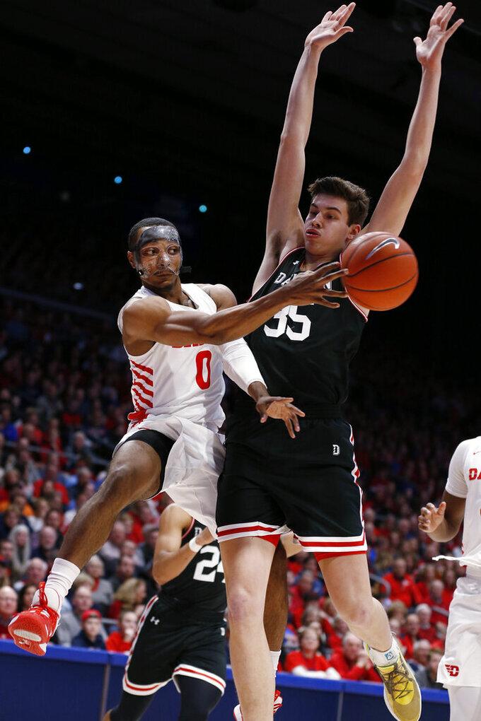 Dayton forward Zimi Nwokeji (0) passes the ball in frront of Davidson forward Luka Brajkovic (35) during the first half of an NCAA college basketball game Friday, Feb. 28, 2020, in Dayton, Ohio. (AP Photo/Gary Landers)