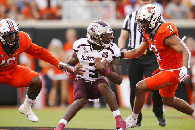 Oklahoma State linebacker Devin Harper, left, and safety Tre Sterling, right, move in to tackle Missouri State quarterback Jason Shelley, center, in the first half of an NCAA college football game, Saturday, Sept. 4, 2021, in Stillwater, Okla. (AP Photo/Sue Ogrocki)