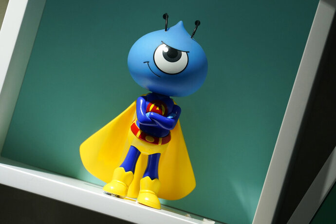 In this Friday, Oct. 23, 2020, photo, the figure of the Ant Group's mascot is displayed at the office in Hong Kong. The world's largest fintech company, China's Ant Group, will try to raise nearly $35 billion in a massive public offering of stock that would shatter records. (AP Photo/Kin Cheung)
