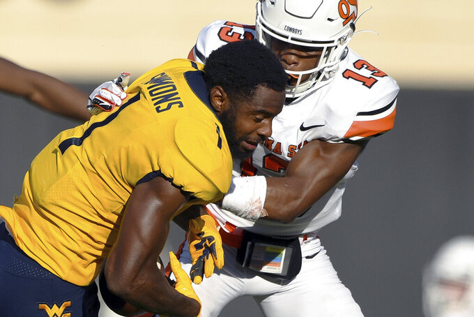 Oklahoma State cornerback Thomas Harper (13) tackles West Virginia wide receiver T.J. Simmons (1), after Simons helmet was removed by Oklahoma State safety Kolby Harvell-Peel (31) during an NCAA college football game Saturday, Sept. 26, 2020, in Stillwater, Okla. (AP Photo/Brody Schmidt)
