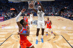 New Orleans Pelicans guard Jrue Holiday (11) slam-dunks over Oklahoma City Thunder guard Shai Gilgeous-Alexander (2) in the first half of an NBA basketball game in New Orleans, Sunday, Dec. 1, 2019. (AP Photo/Gerald Herbert)