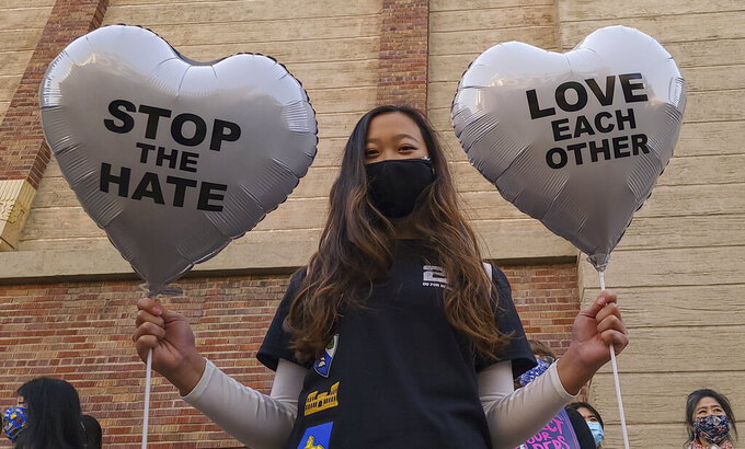 """FILE - In this March 13, 2021, file photo, Chinese-Japanese American student Kara Chu, 18, holds a pair of heart balloons decorated by herself for the rally """"Love Our Communities: Build Collective Power"""" to raise awareness of anti-Asian violence outside the Japanese American National Museum in Little Tokyo in Los Angeles. Asian Americans, already worn down by a year of racist attacks fueled by the pandemic, are reeling but trying to find a path forward in the wake of the horrific shootings at three Atlanta-area massage businesses that left eight people dead, most of them Asian women. (AP Photo/Damian Dovarganes, File)"""