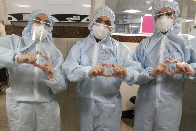 Nurses make a sign of heart with their fingers, in a ward dedicated for people infected with the new coronavirus, at a hospital in Tehran, Iran, Sunday, March 8, 2020. With the approaching Persian New Year, known as Nowruz, officials kept up pressure on people not to travel and to stay home. Health Ministry spokesman Kianoush Jahanpour, who gave Iran's new casualty figures Sunday, reiterated that people should not even attend funerals. (AP Photo/Mohammad Ghadamali)