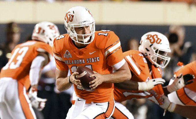 FILE - In this Saturday, Oct. 27, 2018, file photo, Oklahoma State quarterback Taylor Cornelius looks for an open teammate in the second half of an NCAA college football game in Stillwater, Okla. Oklahoma receiver Lee Morris and Oklahoma State quarterback Taylor Cornelius are among the top players in the nation who started their careers as walk-ons. (AP Photo/Brody Schmidt, File)