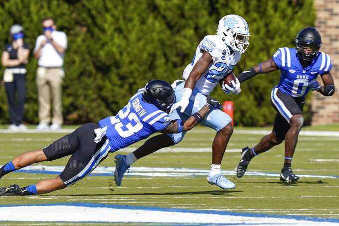 North Carolina running back Javonte Williams (25) is tackled by Duke safety Lummie Young IV (23) and safety Marquis Waters (0) during the first half of an NCAA college football game at Wallace Wade Stadium, Saturday, Nov. 7, 2020, in Durham, N.C. (Jim Dedmon/Pool Photo via AP)