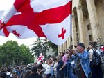 Opposition demonstrators wave a Georgian national flags as they gather in front of the Georgian Parliament building in Tbilisi, Georgia, Monday, June 24, 2019. Demonstrators have returned to parliament for daily rallies, demanding the release of detained protesters, the ouster of the nation's interior minister and changes in the electoral law to have legislators chosen fully proportionally rather than the current mix of party-list and single-mandate representatives. (AP Photo/Shakh Aivazov)