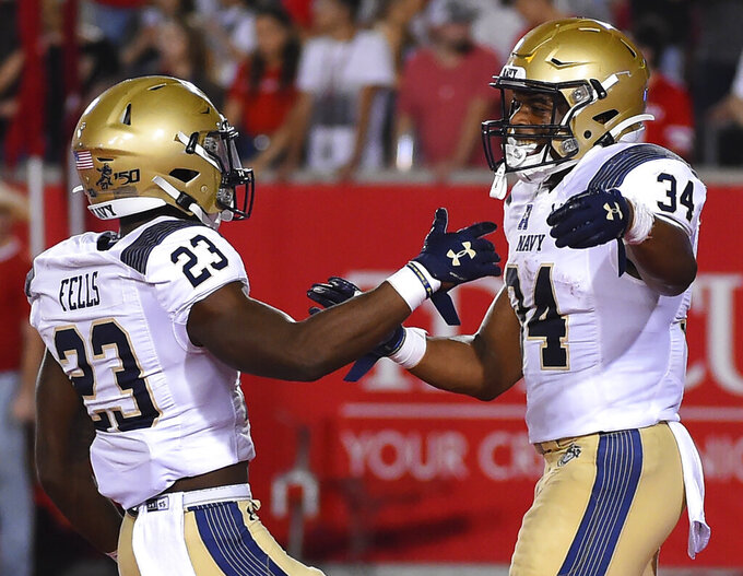 Navy fullback Jamale Carothers (34) celebrates his touchdown with Myles Fells during the first half of an NCAA college football game against Houston, Saturday, Nov. 30, 2019, in Houston. (AP Photo/Eric Christian Smith)