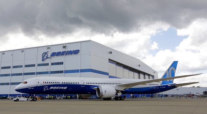 FILE - In this March 31, 2017, file photo, Boeing employees stand near the new Boeing 787-10 at the company's facility in North Charleston, S.C. Federal officials are seeking to fine Boeing $1.25 million, saying Wednesday, Aug. 5, 2020, that company managers pressured employees who were designated to perform safety-related work at the plant. The Federal Aviation Administration said that for nearly two years Boeing made employees doing safety checks report to managers who weren't in position to oversee the work. (AP Photo/Mic Smith, File)