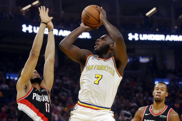 Golden State Warriors forward Eric Paschall (7) shoots between Portland Trail Blazers forward Skal Labissiere, left, and forward Rodney Hood during the first half of an NBA basketball game in San Francisco, Monday, Nov. 4, 2019. (AP Photo/Jeff Chiu)