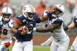 Auburn running back D.J. Williams (3) stiff-arms Samford linebacker Jaleel Laguins (48) as he carries the ball during the first half of an NCAA college football game, Saturday, Nov. 23, 2019, in Auburn, Ala. (AP Photo/Butch Dill)