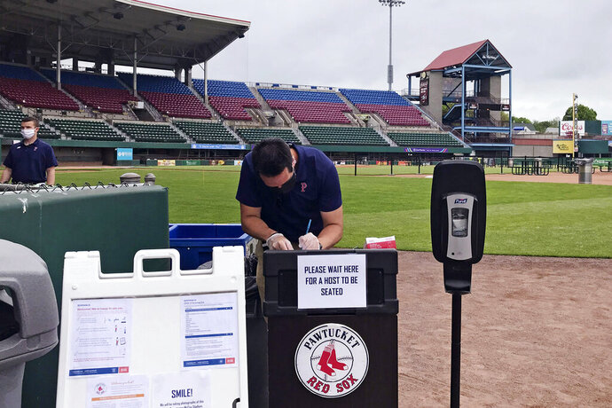 "A worker prepares for guests to dine on the field at McCoy Stadium, home of the Pawtucket Red Sox, in Pawtucket, Rhode Island, Wednesday, May 27, 2020. With the minor league baseball season on hold due to the coronavirus pandemic, the Triple-A affiliate of the Boston Red Sox had found another use for its home field. Starting next weekend, ""Dining on the Diamond"" will allow PawSox fans and others just longing for a taste of baseball to sample typical ballpark fare on the McCoy Stadium infield.(AP Photo/Jimmy Golen)"