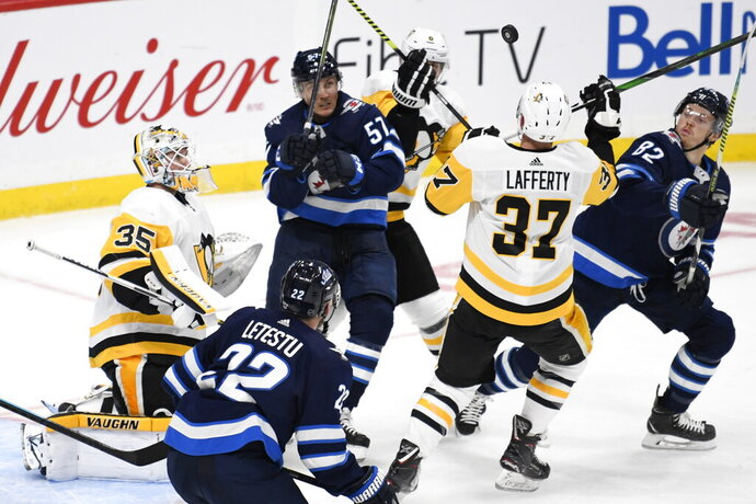 Pittsburgh Penguins goaltender Tristan Jarry (35), Sam Lafferty (37) and Winnipeg Jets' Gabriel Bourque (57) and Mason Appleton (82) follow the bouncing puck during the third period of an NHL hockey game, Sunday, Oct. 13, 2019, in Winnipeg, Manitoba. (Fred Greenslade/The Canadian Press via AP)