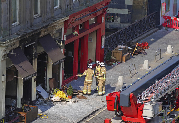 Firefighters at the scene after a fire at the Elephant House Cafe in Edinburgh, Wednesday, Aug. 25, 2021. An Edinburgh cafe where author J.K. Rowling wrote some of the Harry Potter books has been damaged in a fire. The Elephant House in the Scottish capital was blackened by a blaze which broke out at the patisserie next door on Tuesday. (Andrew Milligan/PA via AP)