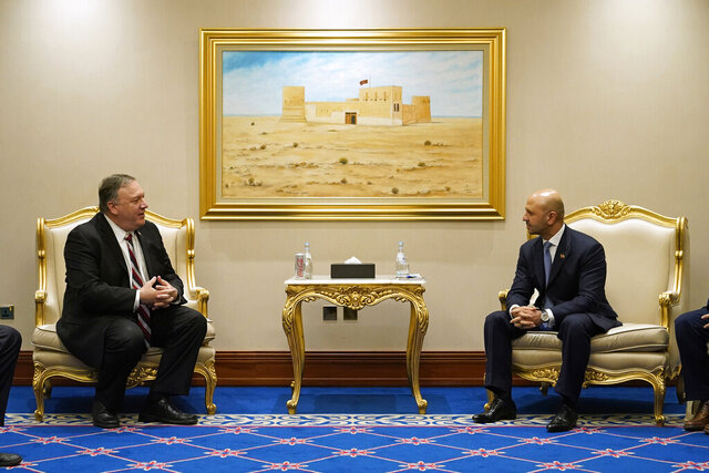 FILE - In this Nov. 21, 2020 file photo, Secretary of State Mike Pompeo, left, meets with Afghanistan's State Minister for Peace Sayed Sadat Mansoor Naderi and the Islamic Republic of Afghanistan's peace negotiation team amid talks between the Afghan government and the Taliban, in Doha, Qatar. A Democratic senator is calling on the State Department to prioritize the return of Mark Frerichs, an American contractor believed to have been taken by a Taliban-linked militant network in Afghanistan earlier this year.  The letter from Sen. Tammy Duckworth of Illinois comes weeks after Secretary of State Mike Pompeo held what are likely his last meetings with the Taliban and Afghan government negotiators trying to hammer out a peace deal. It is unclear to what extent Frerichs, who is one of Duckworth's constituents, was discussed during those meetings. (AP Photo/Patrick Semansky, Pool)