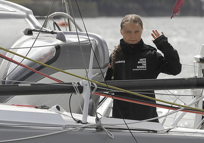 Climate change activist Greta Thunberg waves from the Malizia II boat in Plymouth, England, Wednesday, Aug. 14, 2019. The 16-year-old climate change activist who has inspired student protests around the world will leave Plymouth, England, bound for New York in a high-tech but low-comfort sailboat.(AP Photo/Kirsty Wigglesworth, pool)