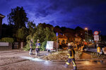 Thunderstorms and heavy rain showers pass over the district of Holtenau, in Kiel, Germany, where a fallen tree is blocking a road, which is inspected by fire brigade emergency services, Monday, July 26, 2021. (Axel Heimken/dpa via AP)