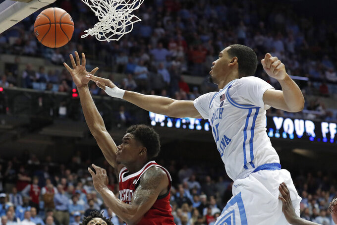North Carolina forward Garrison Brooks, right, blocks North Carolina State guard Markell Johnson during the second half of an NCAA college basketball game in Chapel Hill, N.C., Tuesday, Feb. 25, 2020. (AP Photo/Gerry Broome)