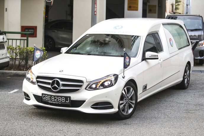 A hearse carrying the body of former Zimbabwe President Robert Mugabe leaves the Singapore Casket Funeral Parlour for the airport in Singapore Wednesday, Sept. 11, 2019. Mugabe died Friday, Sept. 6 at a hospital in Singapore at age 95. (AP Photo/Danial Hakim)