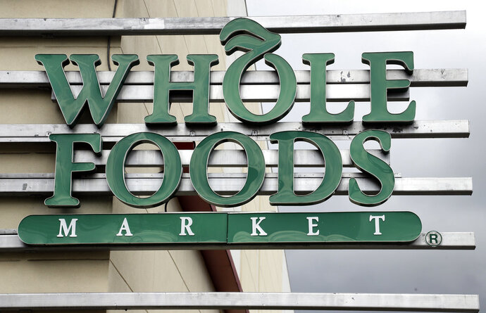 FILE - In this Monday, Aug. 28, 2017, file photo, a sign at a Whole Foods Market greets shoppers in Tampa, Fla. Amazon is bringing its Prime membership to Whole Foods, giving members special discounts and deals at the organic grocer. The new benefits will start Wednesday, May 16, 2018, at Whole Foods stores in Florida, and then rollout nationwide in the summer. Amazon declined to say if it plans to add the benefit to stores in Canada and the United Kingdom. (AP Photo/Chris O'Meara, File)