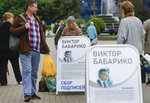 People pass informational posters for Viktar Babaryka, potential candidate in the upcoming presidential elections, in Minsk, Belarus, Sunday, June 14, 2020. The presidential campaign is underway in Belarus despite the coronavirus outbreak after the parliament and government refused to postpone the election scheduled for August 9. (AP Photo/Sergei Grits)