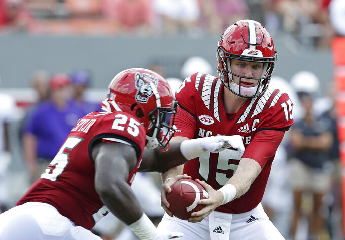 North Carolina State quarterback Ryan Finley hands the ball off to Reggie Gallaspy II (25) during the second half an NCAA college football game against James Madison in Raleigh, N.C., Saturday, Sept. 1, 2018. North Carolina State won 24-13. (AP Photo/Gerry Broome)